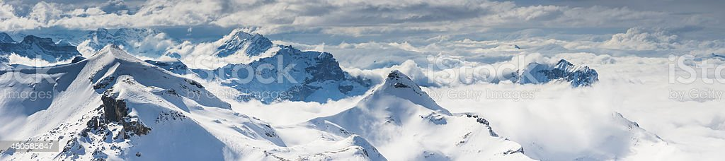 Snowy mountain summits soaring above the clouds Alps Switzerland panorama royalty-free stock photo