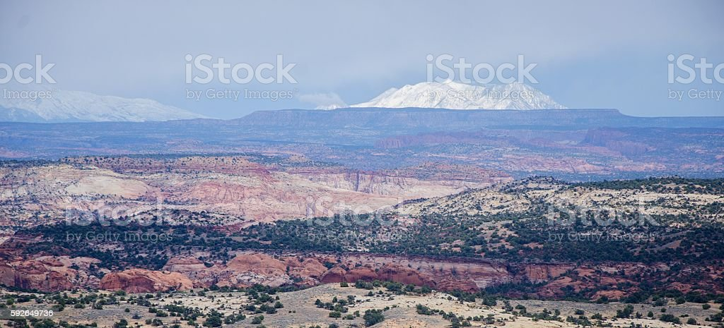 Snowy mountains appearing in the background of an arid landscape stock photo
