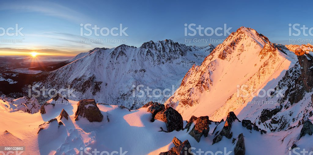 Snowy mountains under orange sunset sky stock photo