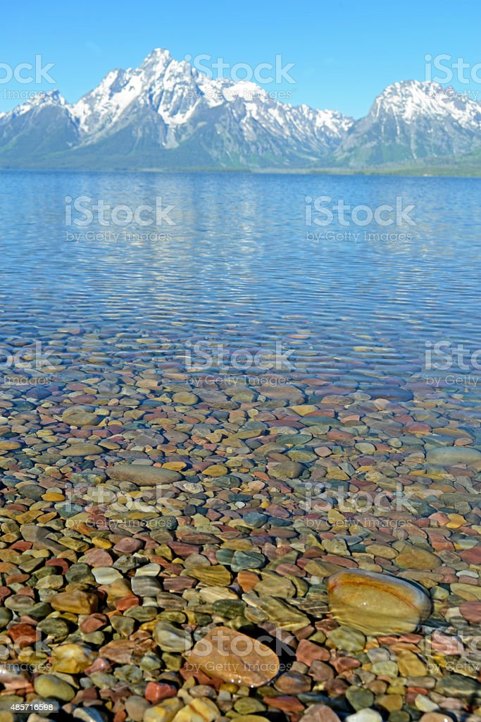 Snowy moutains frame a clear lake and pebbles. stock photo