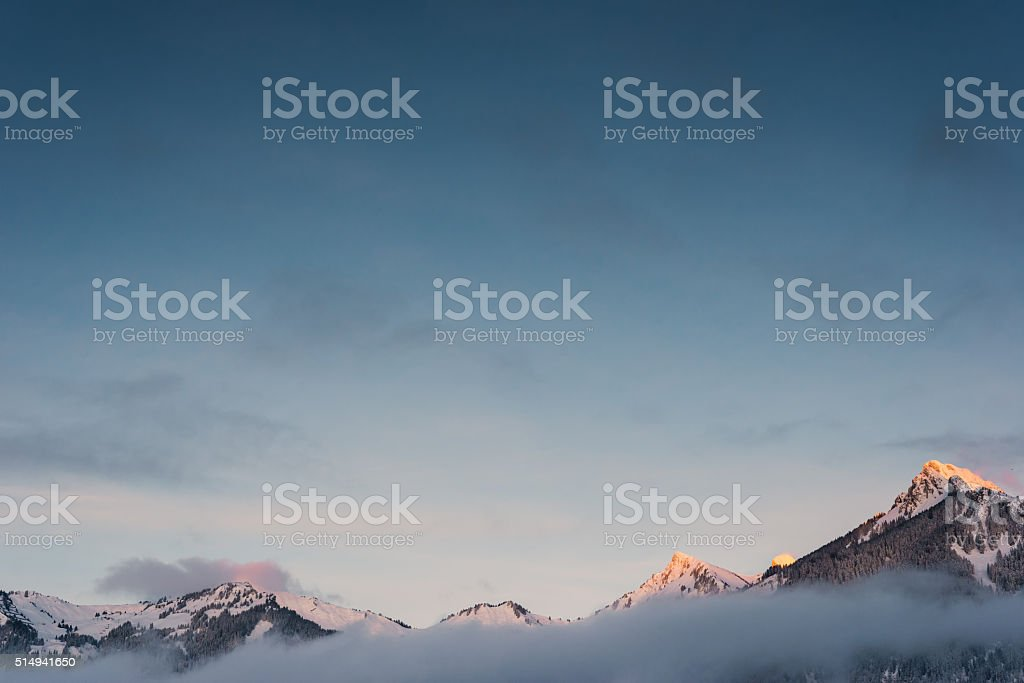 snowy orange peaks of mountain chain in winter with fog stock photo