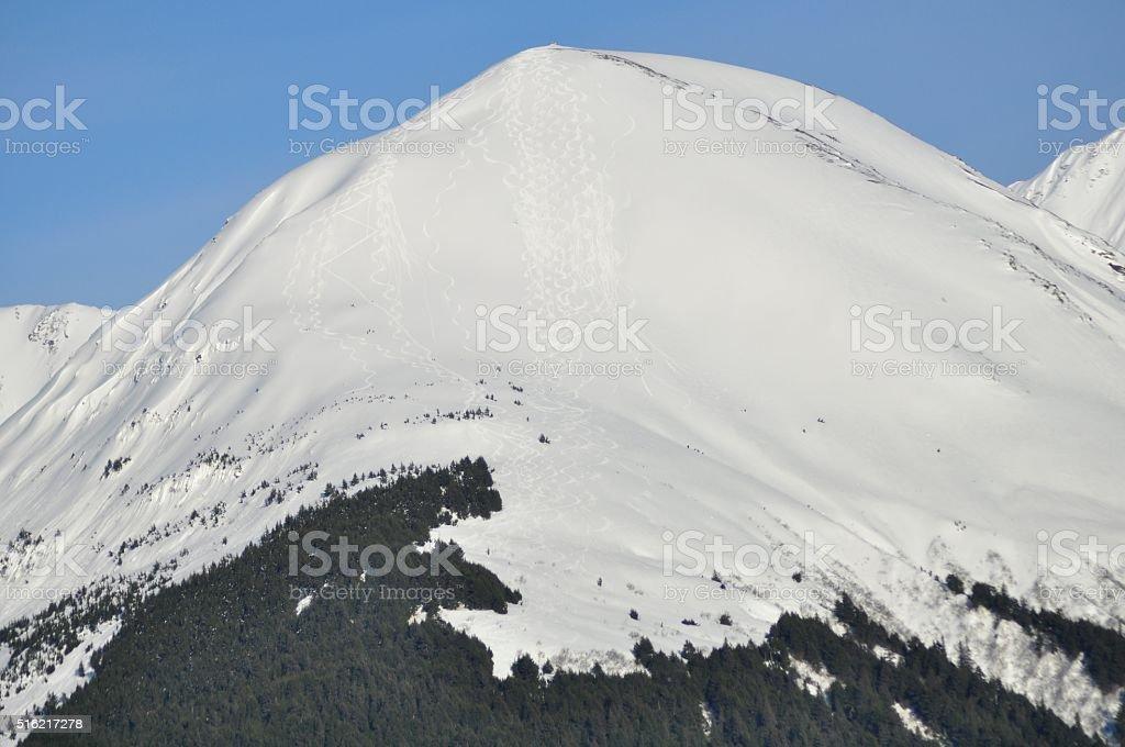 Snowy Peak with Backcountry Ski Tracks in Powder stock photo