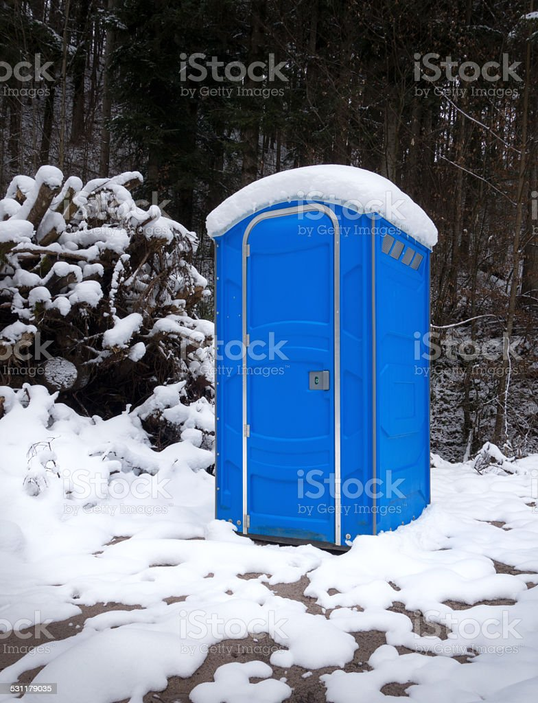 Snowy portable toilet in the forest royalty-free stock photo