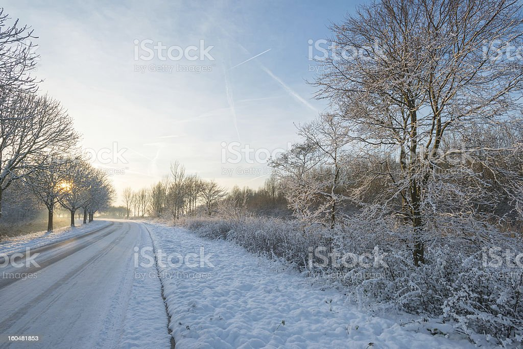 Snowy road at sunset royalty-free stock photo