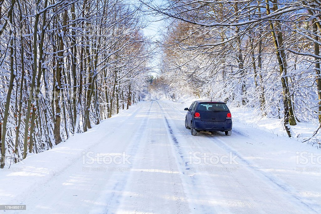 Snowy road in winter forest with single car royalty-free stock photo