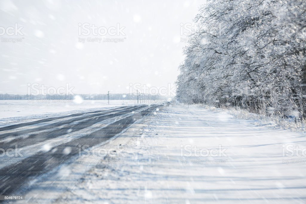 Snowy road through the forest, day. stock photo
