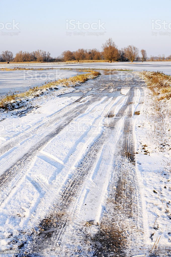 snowy road under water by river stock photo