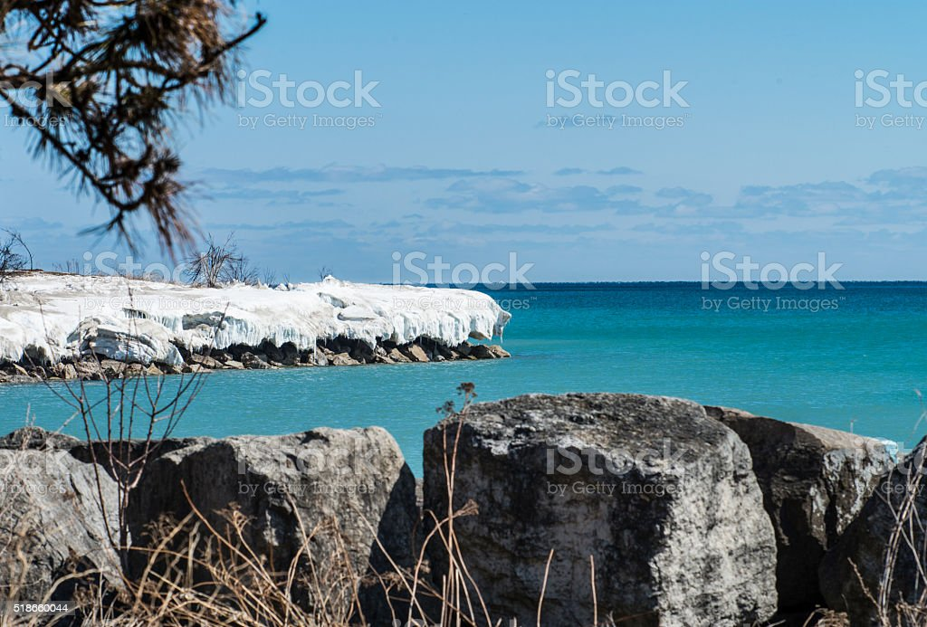 Snowy shore, turquoise water, blue sky, stones on Ontario Lake stock photo