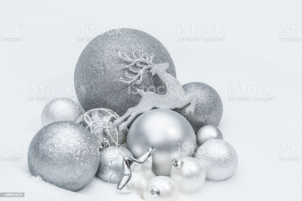 Snowy silver decorative Christmas ornaments with reindeer at ground level stock photo