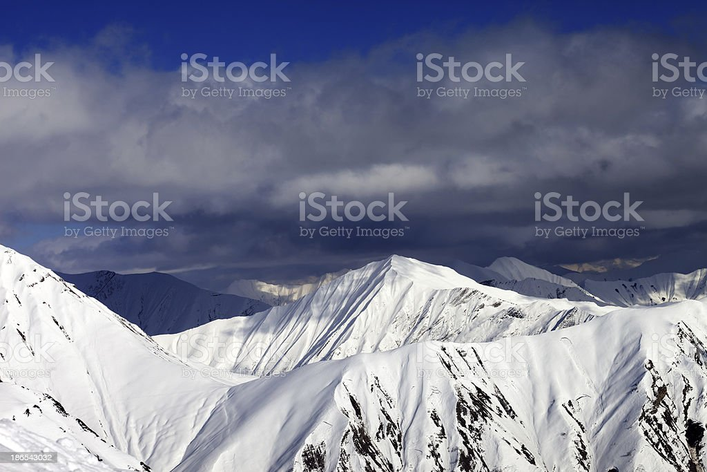 Snowy sunlit mountains and cloudy sky royalty-free stock photo
