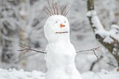 Snowy white snowman with carrot nose in winter Christmas background