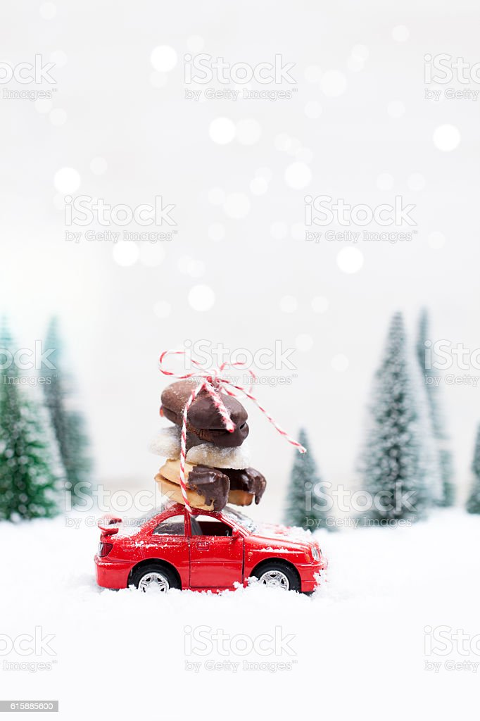 Snowy Winter Forest with miniature red car and cookies stock photo