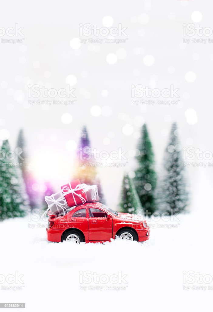 Snowy Winter Forest with  red car carrying christmas presents stock photo