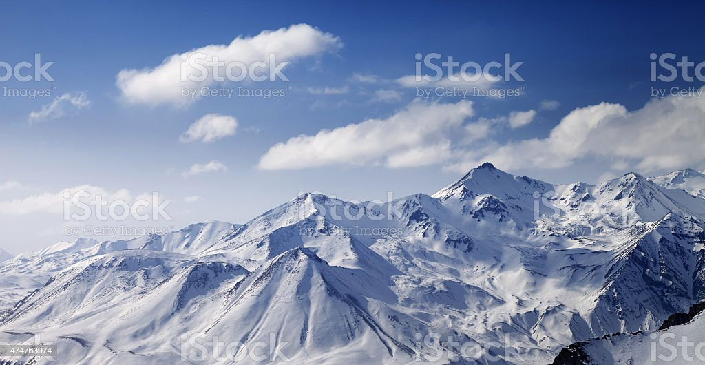 Snowy winter mountains in sun day. Panoramic view. stock photo
