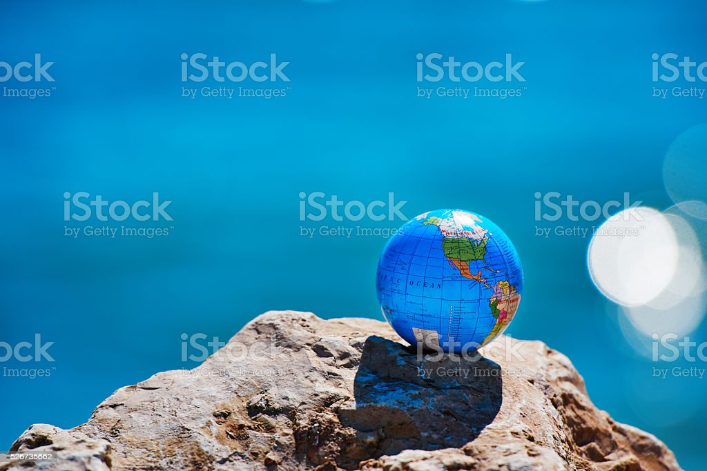 the earth globe on rocks with the sea side in background.