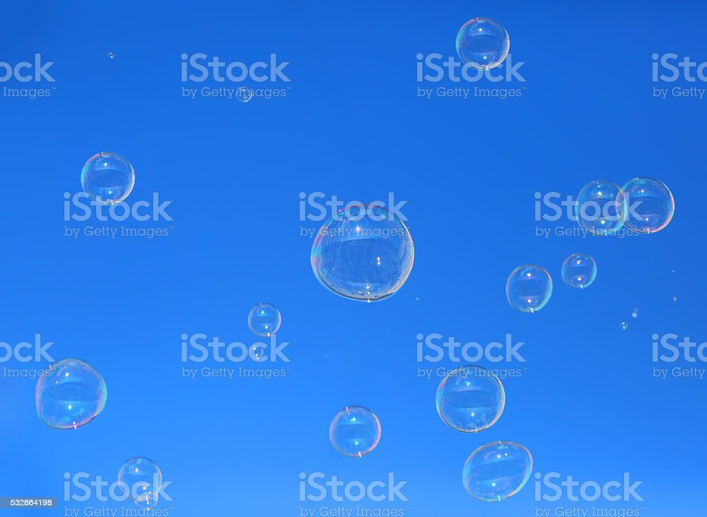 Soap bubbles floating in blue sky stock photo
