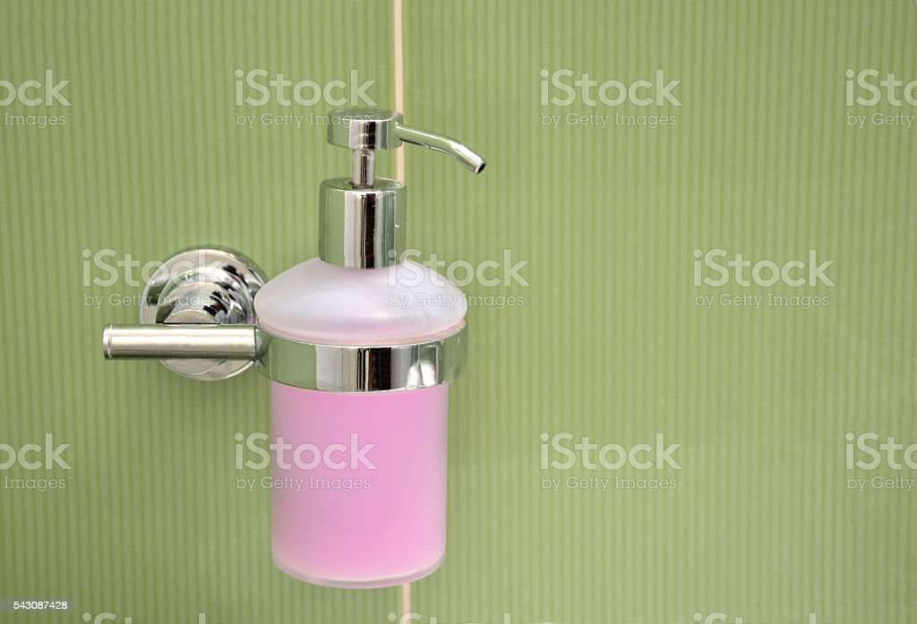Soap container filled with purple foam fixed to green tile stock photo