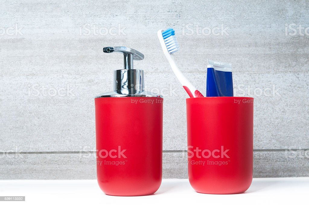 Soap dispenser and toothbrush glass in bathrrom stock photo