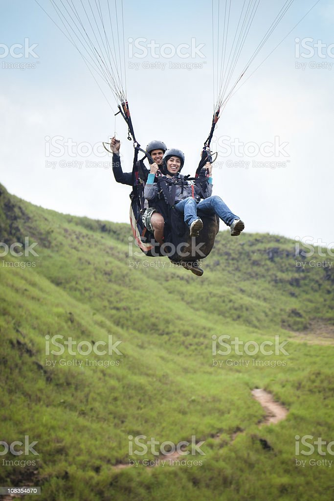 Soaring - Young couple doing tandem paragliding royalty-free stock photo
