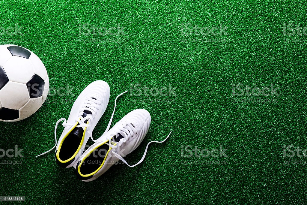Soccer ball and cleats against green artificial turf, studio sho stock photo