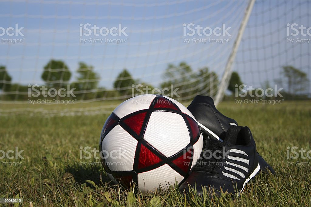Soccer ball and cleats in front of net royalty-free stock photo