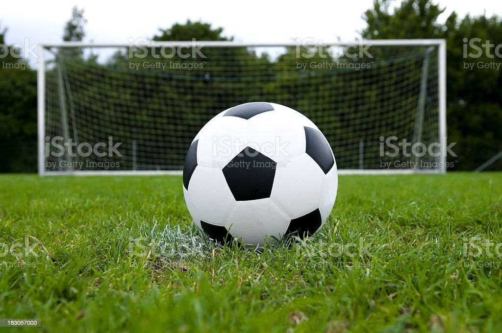 Soccer ball and goal on a football field stock photo