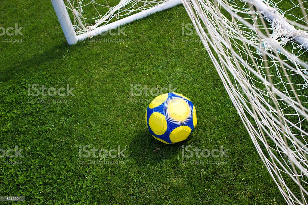 Soccer ball being scored into the net stock photo