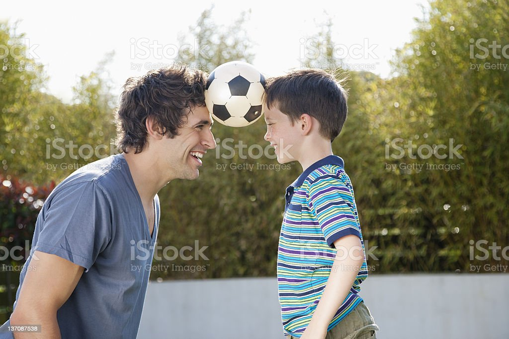 Soccer ball between father and son royalty-free stock photo