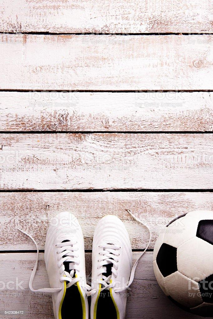 Soccer ball, cleats against wooden floor, studio shot on white...