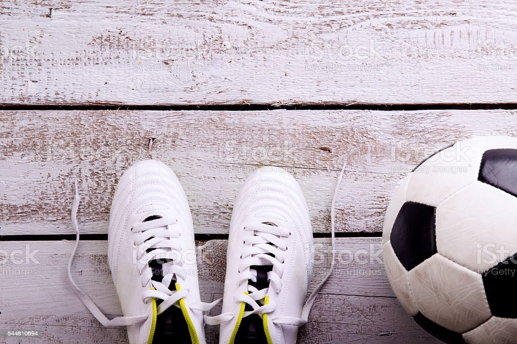 Soccer ball, cleats on white wooden floor, studio shot stock photo