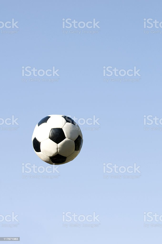 Soccer ball flys through the air on clear blue sky royalty-free stock photo