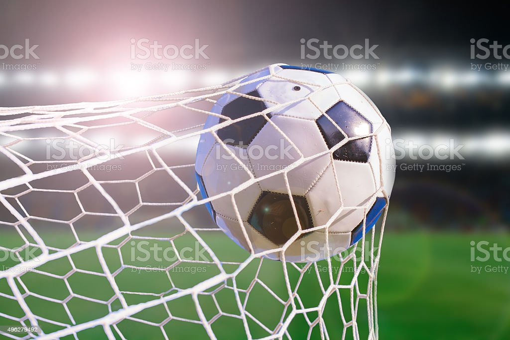 soccer ball hit the net,success goal concept on stadium stock photo