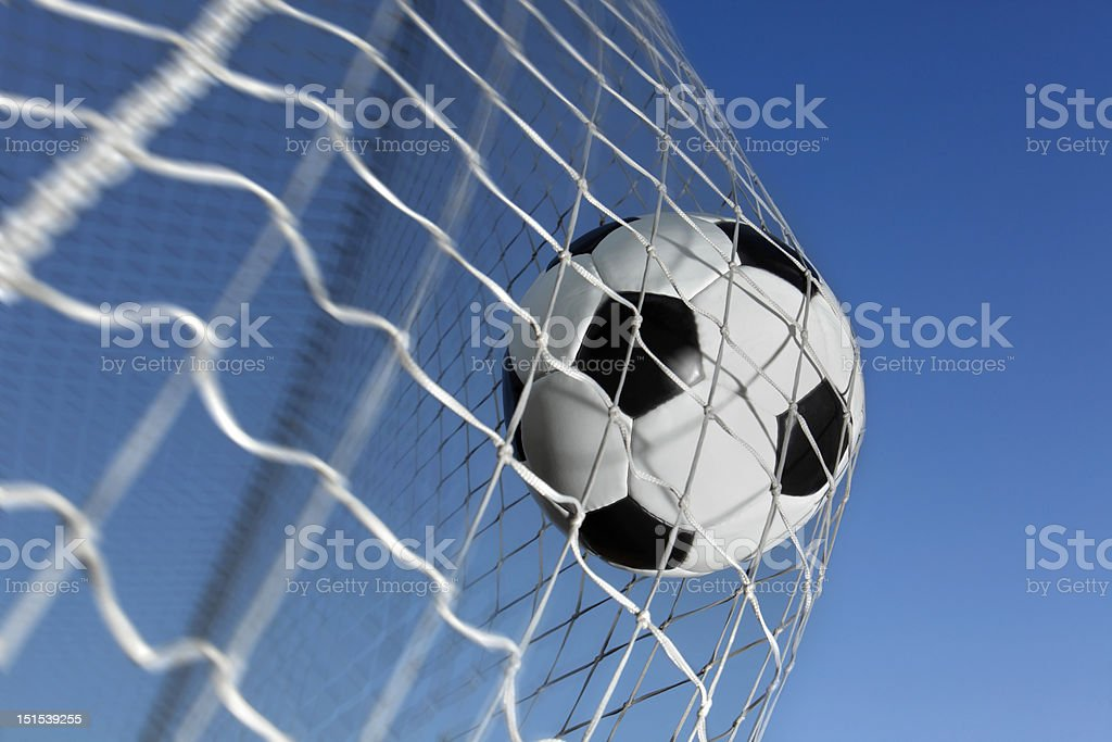 Soccer ball hitting net with blue sky background royalty-free stock photo
