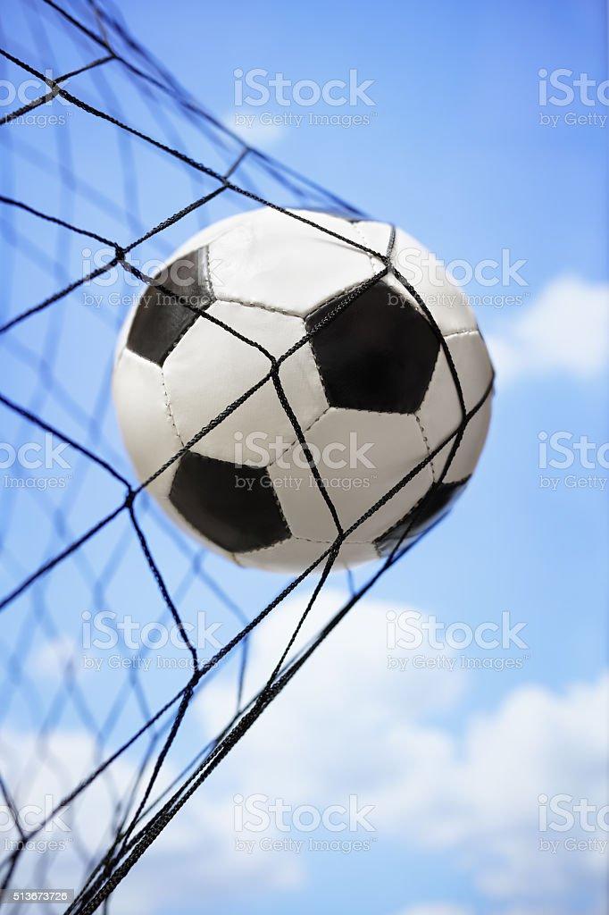 Soccer ball in back of the goal net stock photo