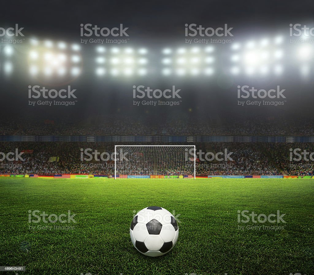 Soccer ball in front of goal posts in stadium stock photo