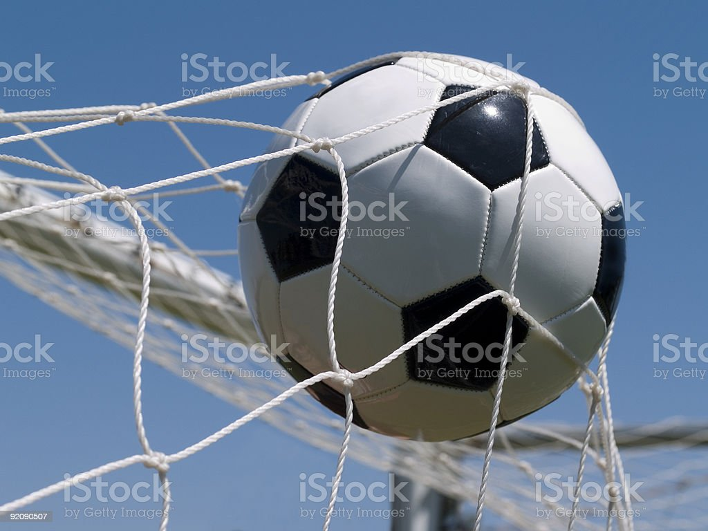 Soccer ball in goal net with blue sky in the background royalty-free stock photo