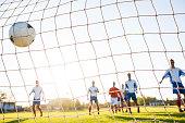 Soccer ball in goalkeeper's net.
