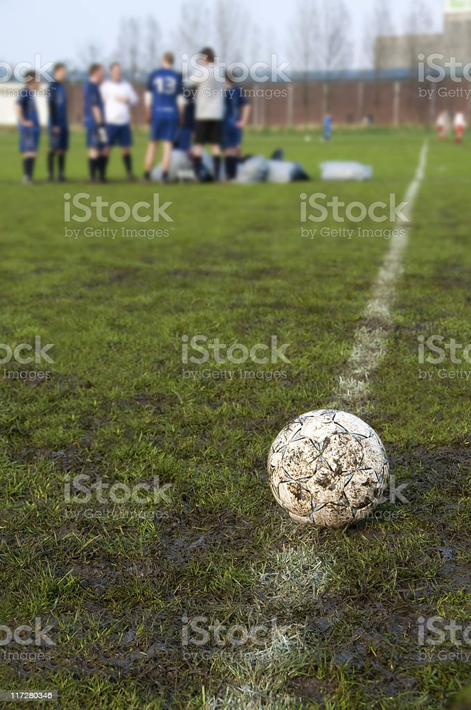 Soccer ball on a muddy football picth before kick off stock photo