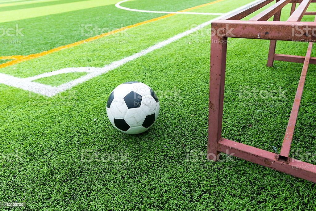 Soccer ball on field and football substitutes seats stock photo