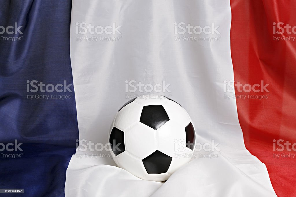 Soccer ball sits centrally on draped French flag stock photo