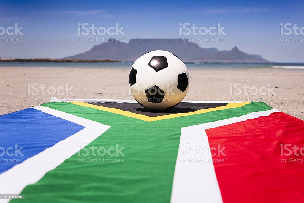 Soccer ball sits on South African flag against Table Mountain royalty-free stock photo