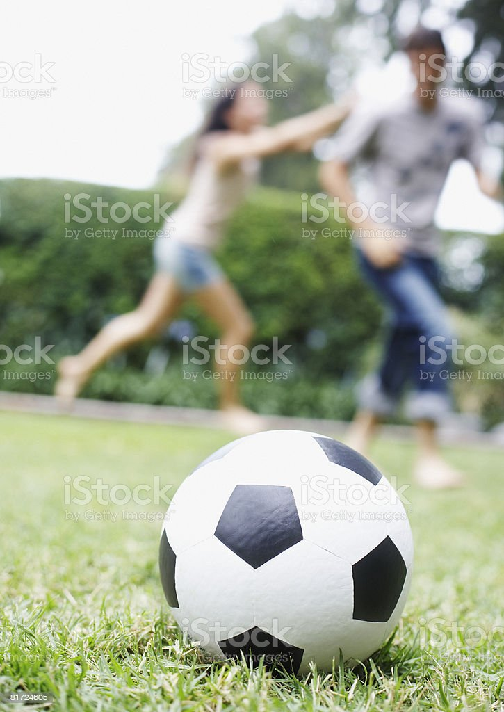 Soccer ball sitting on grass with two people running in background royalty-free stock photo