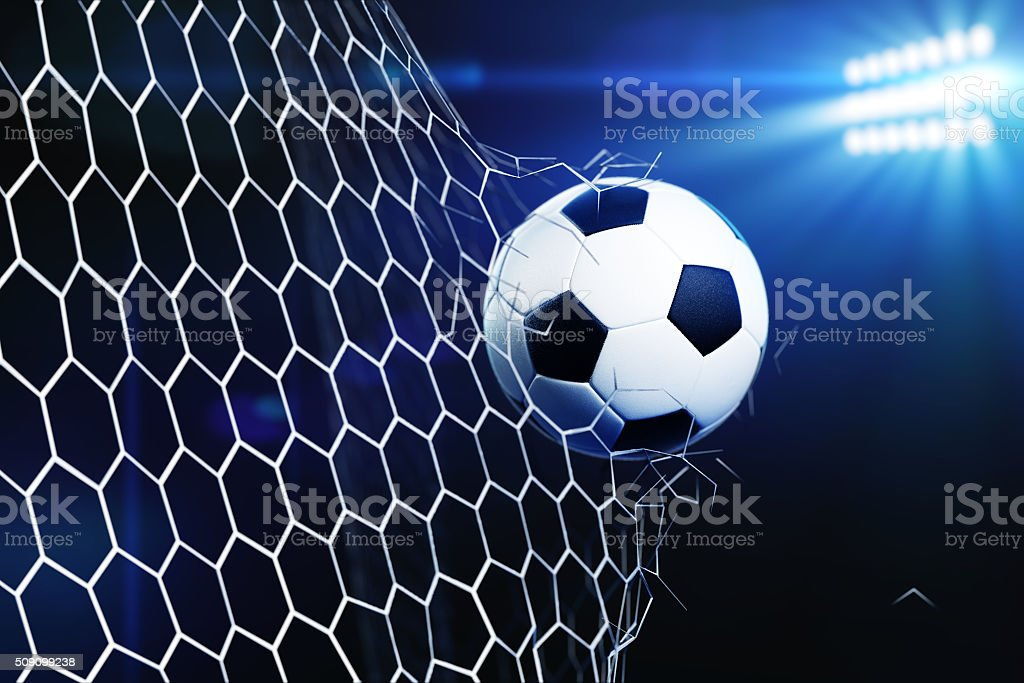 Soccer ball tearing and breaking football goal net stock photo