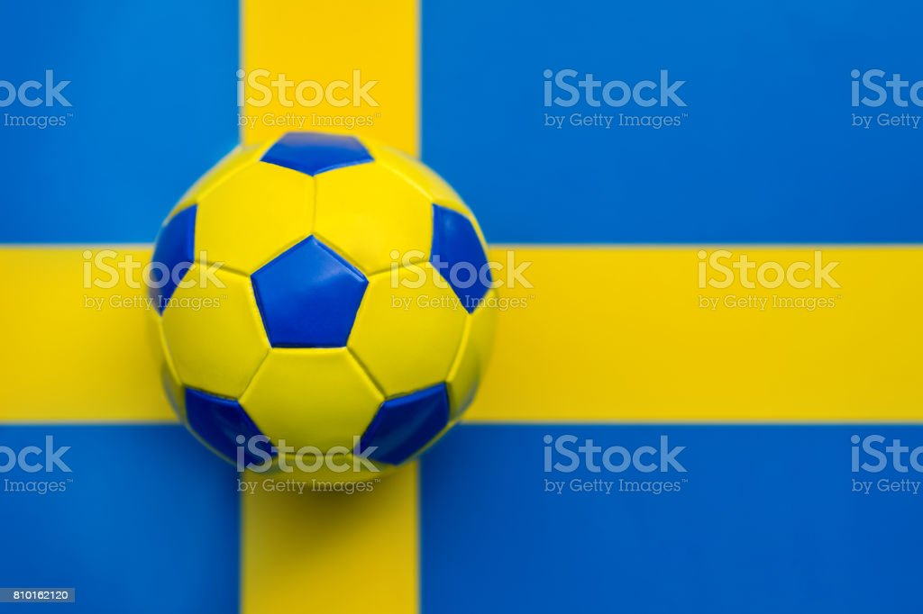 Soccer ball yellow-blue against the background of the flag of the Kingdom of Sweden stock photo