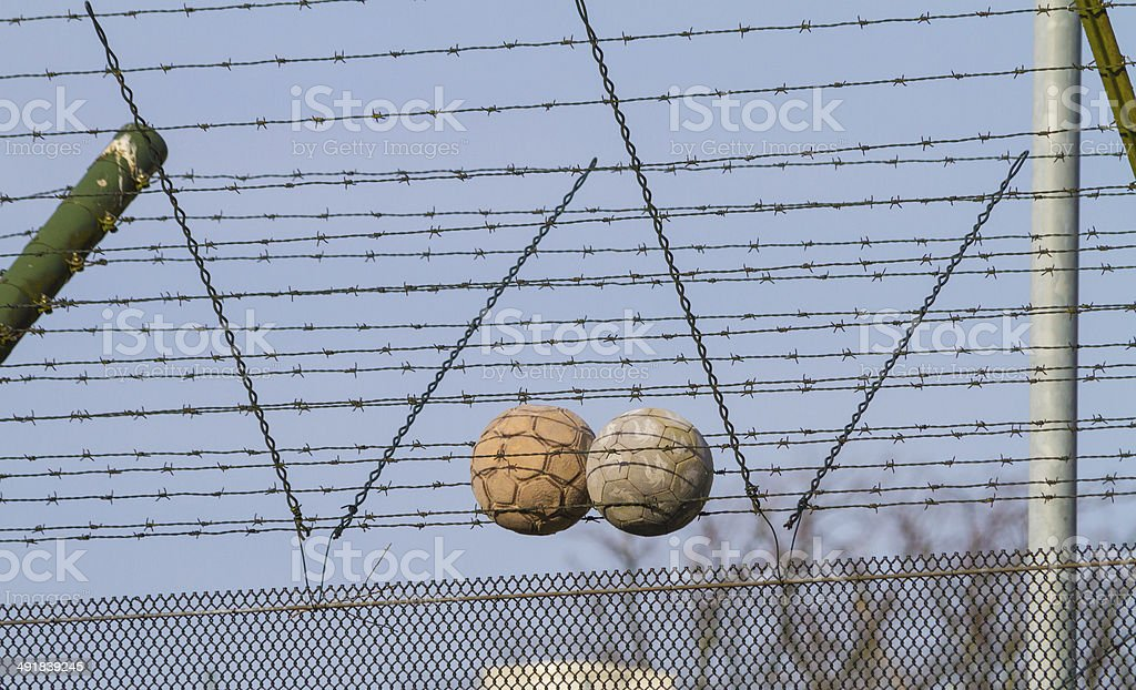Soccer balls on barbed wire on juvenile detention centre fence stock photo