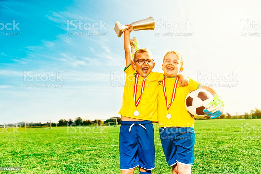 Soccer boys celebrate victory with medals and football stock photo