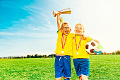 Soccer boys celebrate victory with medals and football