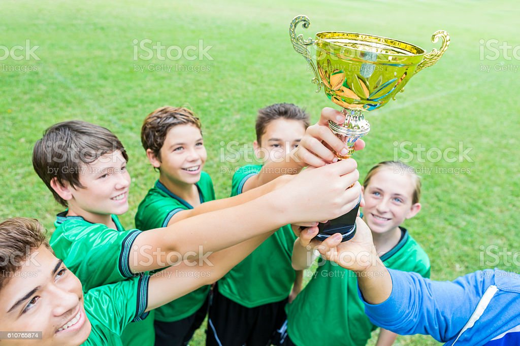 Soccer champs hold trophy up high stock photo
