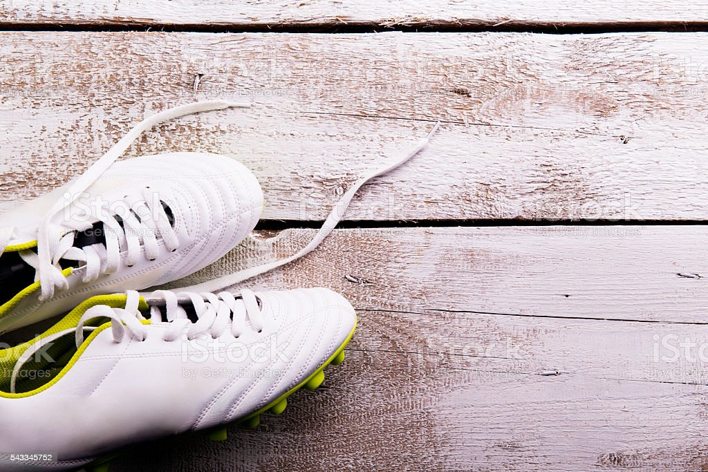 Soccer cleats against wooden background. Studio shot. Copy space. stock photo