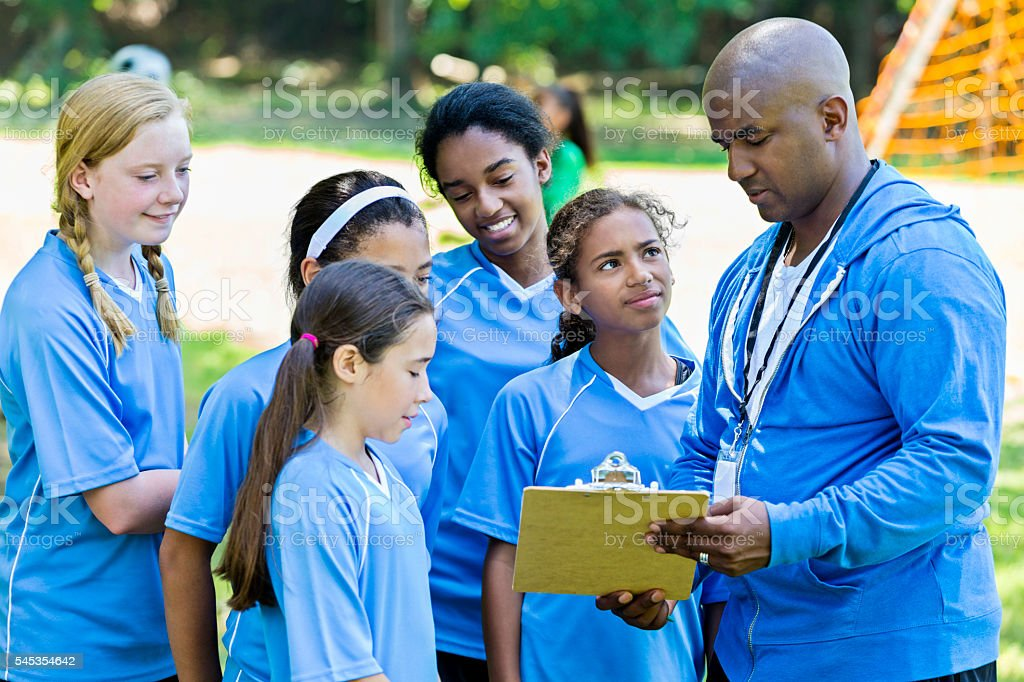 African American soccer coach and his team going over soccer plays...